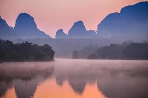 nebliger Sonnenaufgang über Wasser und Bergen