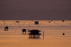 Silhouetten von schwimmenden Hütten bei Sunirse
