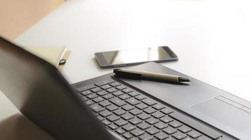 Stift und Telefon mit einem Laptop foto