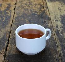Tasse Tee auf hölzernem Hintergrund