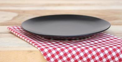 Teller und karierte Tischdecke auf dem Tisch foto