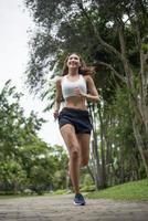 junge sportliche Frau, die im Park läuft