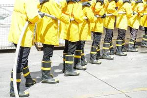 Feuerwehrleute mit Feuerlöscher und Wasser