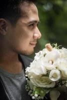Nahaufnahme des Bräutigams mit schönem Blumenstrauß in den Händen für Braut foto