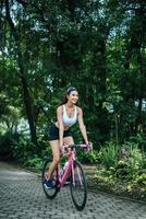 junge Frau, die ein Fahrrad im Park reitet foto
