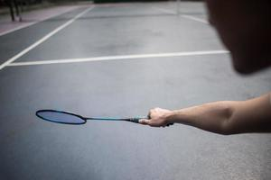 junger Mann, der draußen Badminton spielt foto