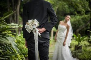 Porträt eines Bräutigams, der einen Blumenstrauß hinter seinem Rücken versteckt, um Braut zu überraschen foto