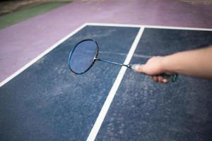 junger Mann, der Badmintonspiel im Freien spielt foto