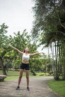 junge sportliche Frau, die sich im Park ausdehnt