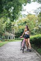 Porträt einer Frau mit einem rosa Fahrrad foto