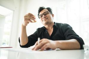 junger Geschäftsmann, der am Schreibtisch trinkt foto