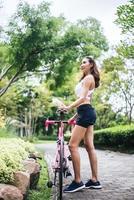 Porträt der jungen Frau mit einem rosa Fahrrad im Park foto