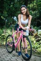 Porträt einer Frau mit einem rosa Fahrrad im Park foto
