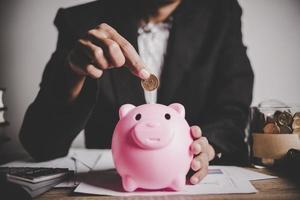 Geschäftsfrau, die eine Münze in ein Sparschwein steckt