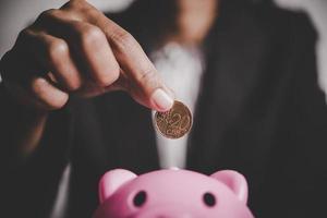 Person, die Münzen in ein Sparschwein auf dem Tisch legt