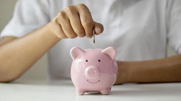 Frauen stecken Silbermünzen in Ferkel, um Geld zu sparen und Geld für zukünftige Investitionen zu sparen. Finanzkonzept foto