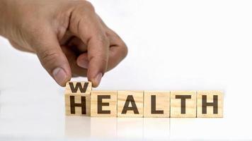 Wenden Sie die Botschaft auf dem Holzblock von Gesundheit zu Wohlstand, Gesundheitskonzept und einer nachhaltigen finanziellen Zukunft