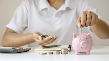 Geldmünzen in Schweinchen stecken Geld sparen, Konzept Geld sparen für die Zukunft im Ruhestand foto