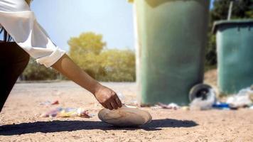 die Hand einer freiwilligen Helferin, die glücklich Plastikmüll im Park sammelt, mit der Idee, im Park aufzuräumen foto