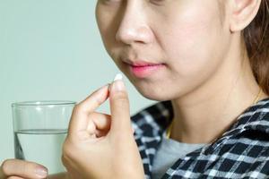 asiatische Frauen, die Medikamente einnehmen foto