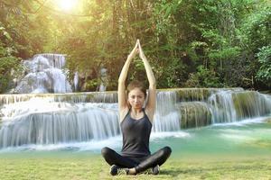 sportliche asiatische Frau in der Yoga-Pose mit Wasserfallhintergrund