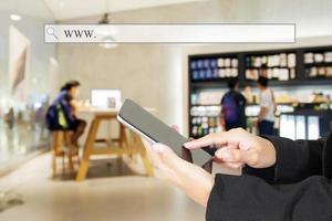 Person, die ein Tablet in einem Geschäft oder Café verwendet