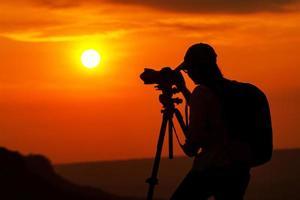 Silhouette der asiatischen Person, die ein Foto im Sonnenuntergang macht