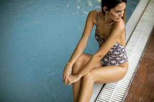 schöne junge Frau, die am Schwimmbad sitzt foto