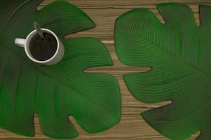 Kaffeetasse und Blätter auf dem Tisch