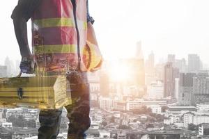 Bauarbeiter, der Werkzeugkasten mit Stadthintergrund hält