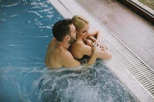 junges Paar, das sich am Pool des Innenpools entspannt foto