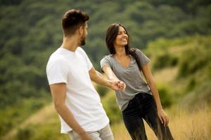 glückliches junges Paar in der Liebe, die durch Grasfläche geht foto