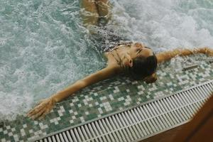 junge Frau, die in der Whirlpool-Badewanne am Pool entspannt foto