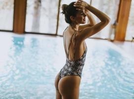 schöne junge Frau, die am Schwimmbad steht foto