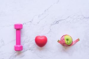 rosa Hantel, rotes Herz und Apfel auf einem Marmorhintergrund