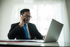 junger Geschäftsmann, der mit Laptop im Büro arbeitet foto