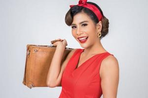 Retro modische Frau hält Gepäck, um zu reisen foto