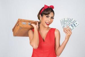 Retro modische Frau hält Gepäck und Geld, um zu reisen foto