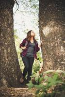 Wanderer, der zur Seite schaut, die im Wald geht foto