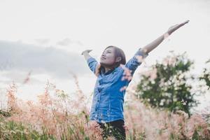 junge schöne Frau streckt ihre Arme in der Luft in einem Feld