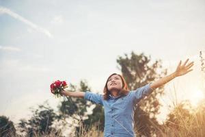 schöne Frau Hipster hebt ihre Arme in der Luft mit Blumenstrauß foto