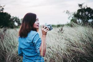 glückliche junge hipster frau mit vintage kamera im feld
