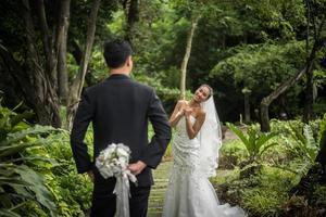 Porträt eines Bräutigams, der Blumenstrauß hinter seinem Rücken versteckt, um Braut zu überraschen foto