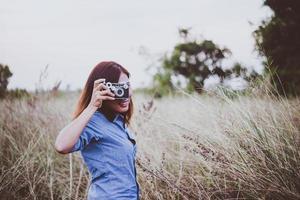 glückliche junge hipster frau mit vintage kamera im feld foto