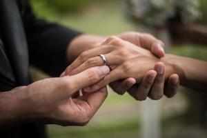 Nahaufnahme des Bräutigams, der Ring auf Braut setzt foto