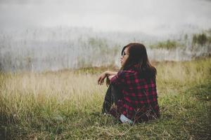junge Hipsterfrau, die auf Gras nahe einem See sitzt foto