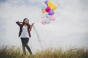 schöne junge Hipsterfrau, die bunte Luftballons draußen hält foto