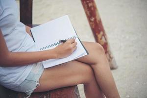schöne junge Frau auf einer Schaukel, die auf ihren Notizblock schreibt foto