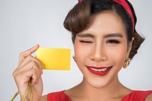 Porträt einer Frau, die eine Kreditkarte hält foto