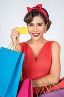 modische Frau, die mit Tasche und Kreditkarte einkauft foto
